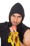 Handsome young strong man holding red apple and Stock Photography