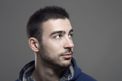 Handsome young stubble man looking up. Close up portrait. Over gray studio background royalty free stock photos