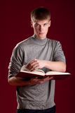 Handsome young student with book stock photo