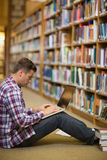 Handsome young student sitting on library floor using laptop. In college Royalty Free Stock Photo