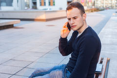 Handsome young student using mobile phone. Stock Photo