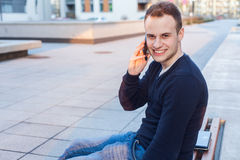 Handsome young student using mobile phone. Handsome young student using mobile phone Royalty Free Stock Images