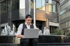 Handsome young student working with laptop outdoors. He is wearing jacket and white shirt, with glasses and black cap Royalty Free Stock Image