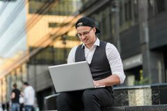 Handsome young student working with laptop outdoors. He is wearing jacket and white shirt, with glasses and black cap, typing, job, finance, city center Royalty Free Stock Images