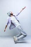 Handsome young stylish man in headphones dancing. Man in pink jacket, grey pants, cap, old sneakers and headphones dancing against grey background Stock Images