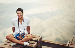 Handsome young stylish men with vintage camera chill out by the Royalty Free Stock Photos