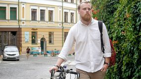 Handsome stylish student with bicycle on street. Handsome young stylish student with bicycle on street Stock Image