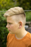Handsome young teenage boy. With a trendy blond hairstyle standing outdoors in the garden, close up head and shoulders profile portrait Stock Image