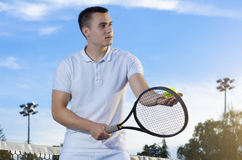 Handsome young tennis player dressed in white Stock Images