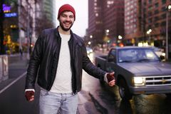 Handsome young tourist Hitchhiking on Road. Catch Car on Highway. Tourism and People Concept. Active Lifestyle. royalty free stock photo