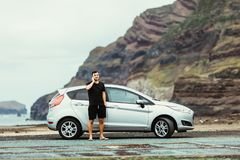 Handsome young traveler man standing outdoors near his car and talking on the mobile phone with ocean and rock background. Young m royalty free stock images