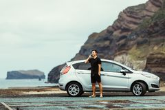 Handsome young traveler man standing outdoors near his car and talking on the mobile phone with ocean and rock background. Young m stock image