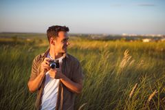 Handsome young traveler man with vintage camera,on a green meadow background. Travel mood. Photography. Relaxation on a field and sunset. Explore nature royalty free stock photo