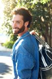 Handsome young traveling man smiling with bag Stock Photography