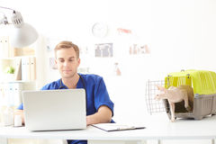 Handsome young veterinarian using computer in clinic Stock Images