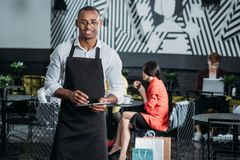 Handsome young waiter in apron standing. At cafe Stock Photography