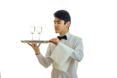 Handsome young waiter with black hair stands straight looks away and holds a tray with two glasses Royalty Free Stock Image