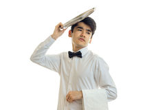 Handsome young waiter got tired and put on the head of an empty dish podnom close-up Royalty Free Stock Image