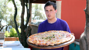 Handsome Young Waiter Portrait. Portrait of a waiter with large family pizza at an outdoor restaurant Royalty Free Stock Photo