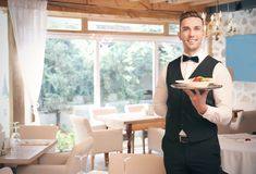 Handsome young waiter. At restaurant stock photo