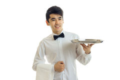 Handsome young waiter stretches forward tray for cupboards and smiling Stock Image