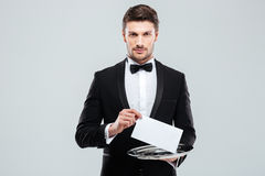 Handsome young waiter in tuxedo holding tray Royalty Free Stock Image