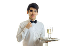 Handsome young waiter in a white shirt smiling and holding two glasses of champagne on a tray that Royalty Free Stock Image