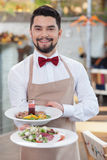 Handsome young waiter is working in restaurant Royalty Free Stock Images