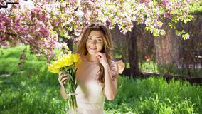 Handsome young woman with bouquet of tulips among flowering garden. Attractive woman at spring concept. Medium shot. Petals falls stock video footage