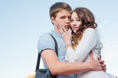 Handsome young woman embrace her sad and serious boyfriend posing. Stock Images