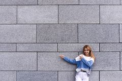 Handsome young woman is pointing away, looking at camera and smiling, standing against gray wall. stock photography