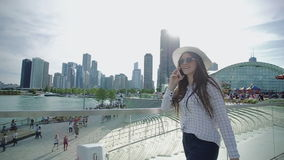Handsome young woman slowly walks on embankment and talks on smartphone. stock video footage