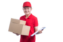 Handsome young worker in red t-shirt and cap smiling, holding a Stock Image