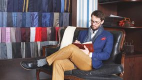 Handsome young writer in a classy suit having an inspiration mood making some notes , while sitting on vintage sofa.