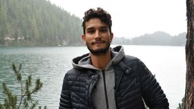 Young man relaxing at mountain lake. Handsome yung man standing by mountain lake, on background of woods looking at camera with a smile. Braies lake or Pragser stock footage