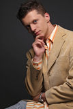 A handsomee fashion model. In a beige jacket on a stool Royalty Free Stock Photo