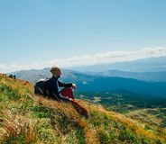 Handsomeyoung man sitting on rocky cliff and enjoying nature Royalty Free Stock Photography
