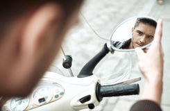 Handsomke man looking at himself in bike's mirror Royalty Free Stock Image