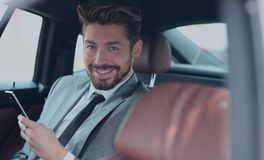 Happy young businessman using mobile phone in back seat of car. Handsone successful businessman using mobile phone in back seat of car Stock Photo