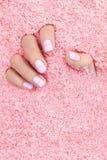 Handsorgfalt Hand mit Pastellnägeln im Seesalz stockfoto