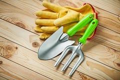 Handspade en tuinvork met gele leerhandschoenen op hout stock foto's