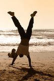 Handstand. Dog watching a boy doing handstand on the beach Stock Images