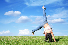 Handstand. A young woman makes a handstand on grass in front of blue sky Royalty Free Stock Photo