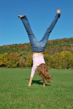 Handstand. Girl doing a handstand in green field Royalty Free Stock Photo