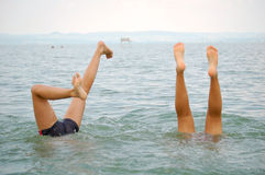 Handstand. Girl and boy do a handstand in the lake Stock Photo