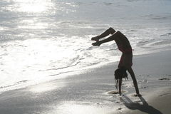 Handstand. Girl doing a handstand at the beach by the water Royalty Free Stock Photography