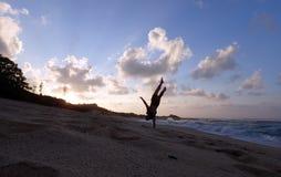 Το άτομο κάνει ένα χέρι Handstand στην παραλία στο ηλιοβασίλεμα Στοκ Φωτογραφίες
