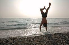 Handstand auf dem Strand lizenzfreie stockfotos