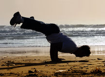 Handstand on the beach. Silhouette Stock Photos