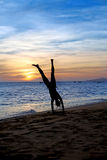 Handstand  on the beach. Silhouette young woman making a handstand  on a beach. Sunset Stock Images